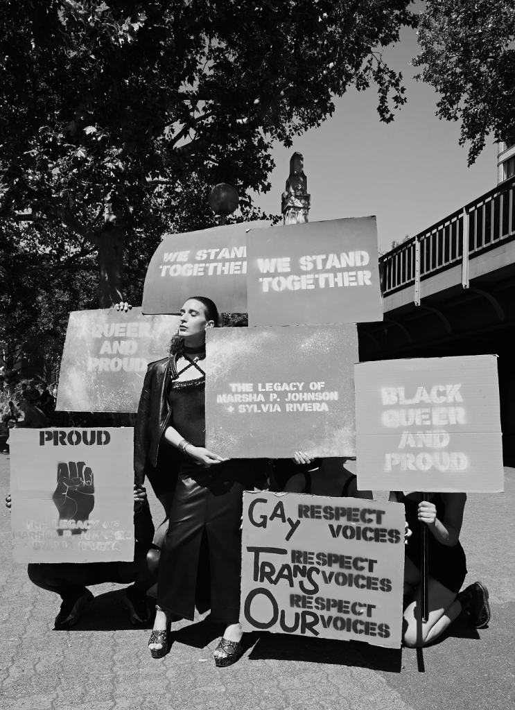 """Photo showing Ria with other members of the House of Saint Laurent at the Pride March in Berlin 2020. Posters read: """"We stand together"""", """"Black Queer and Proud"""", """"The Legacy of Marsha P. Johnson + Sylvia Rivera"""", """"Respect GAY Voices, Respect TRANS Voices, Respect OUR Voices"""", """"Queer and Proud"""""""