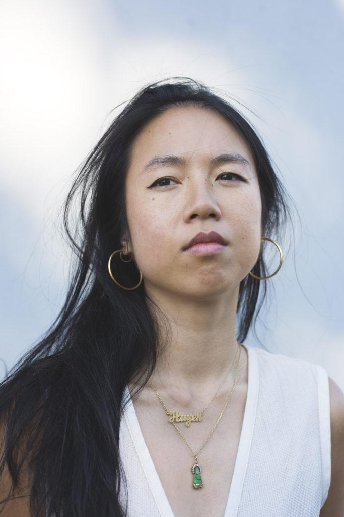 """Thị Minh Huyền Nguyễn blinkt an der Kamera vorbei. Sie trägt goldenen Schmuck, unter anderem einen Anhänger mit ihrem Namen """"Huyen"""". Der Hintergrund ist ein blauer, leicht bewölkter Himmel."""