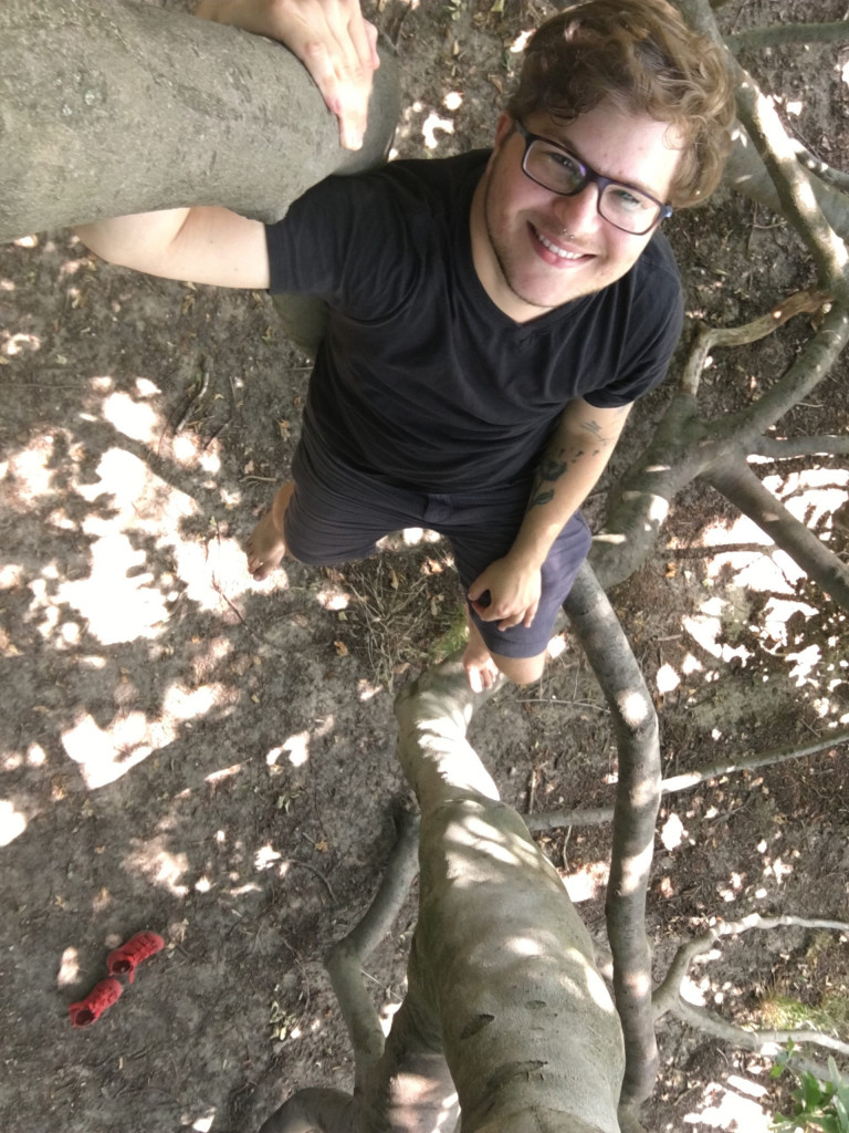 Eno sitzt in einem Baum und blickt hoch in die Kamera. Ey trägt eine Brille und hat ein Tattoo. Das Licht scheint in Flecken durch das Laub auf den Erdboden. Dort stehen ein paar rote Schuhe. Eno ist barfuss.